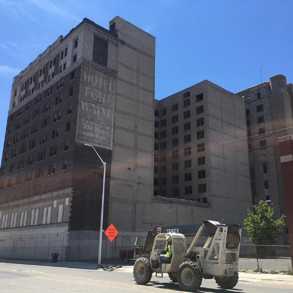 Schnappschuss eines gigantischen, leerstehenden Detroiter Gebäudekomplexes, der früher ein Hotel beherbergte. Auf der Straße vor dem verlassenen Gebäude verrichtet ein Bagger Straßenarbeiten.